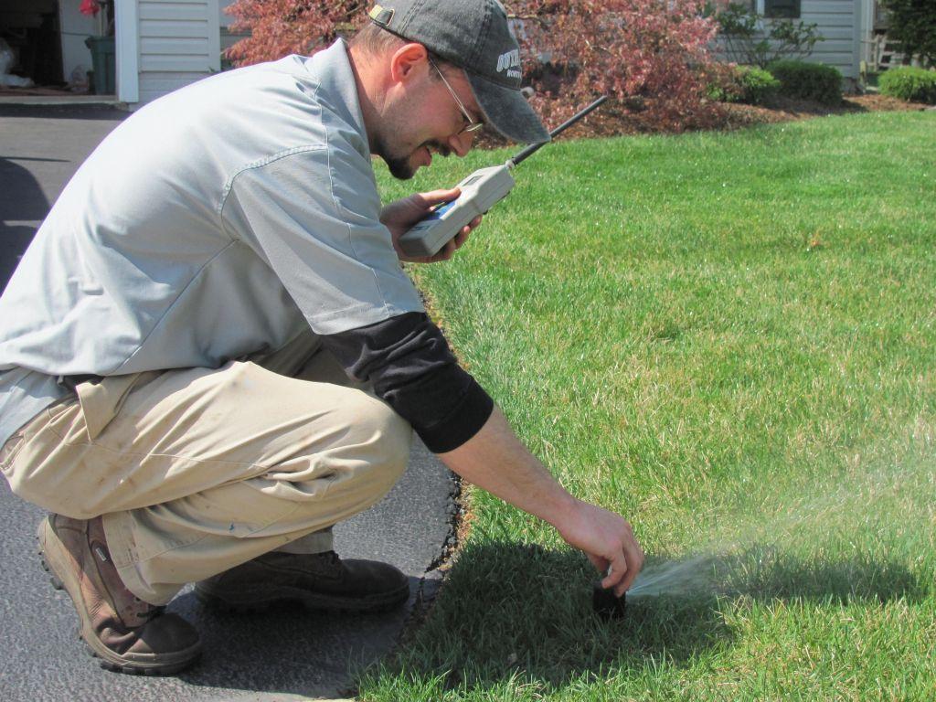 Matt with a remote controller adjusting sprinkler